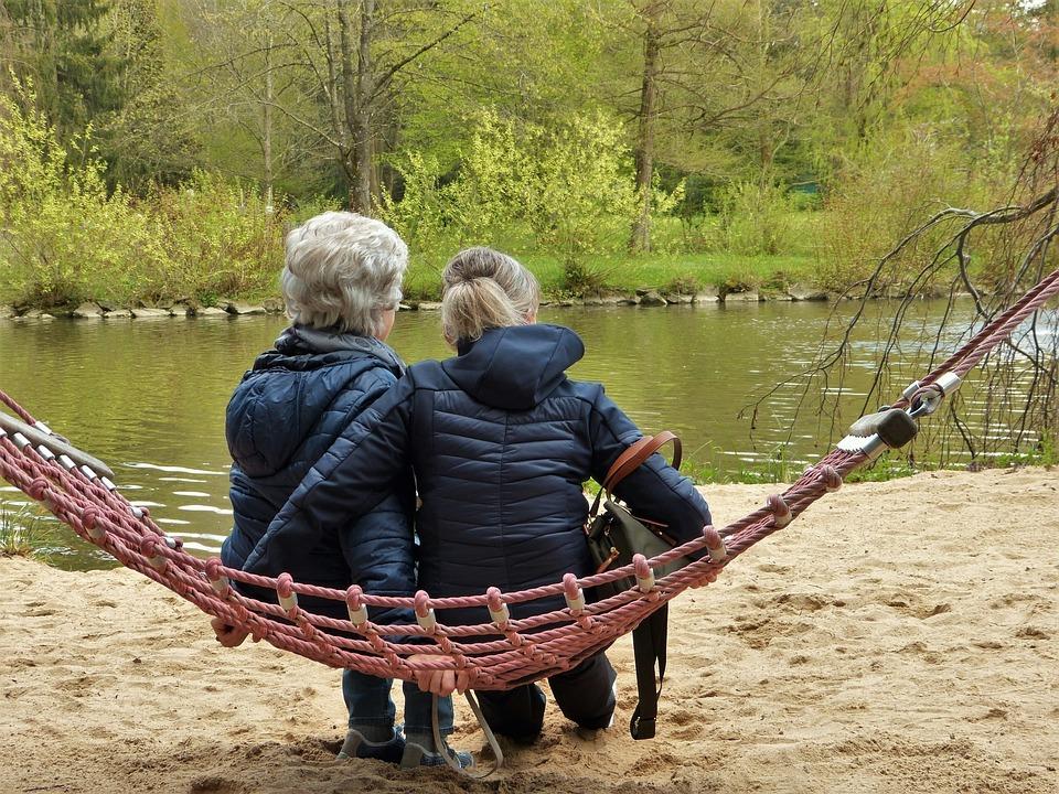 persona mayor junto a su cuidadora en un parque