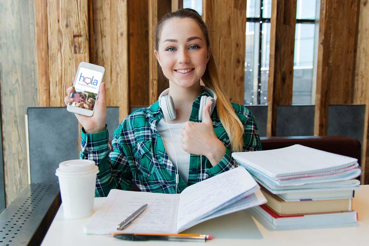 Alumna estudiando sonriendo y mostrando su teléfono móvil