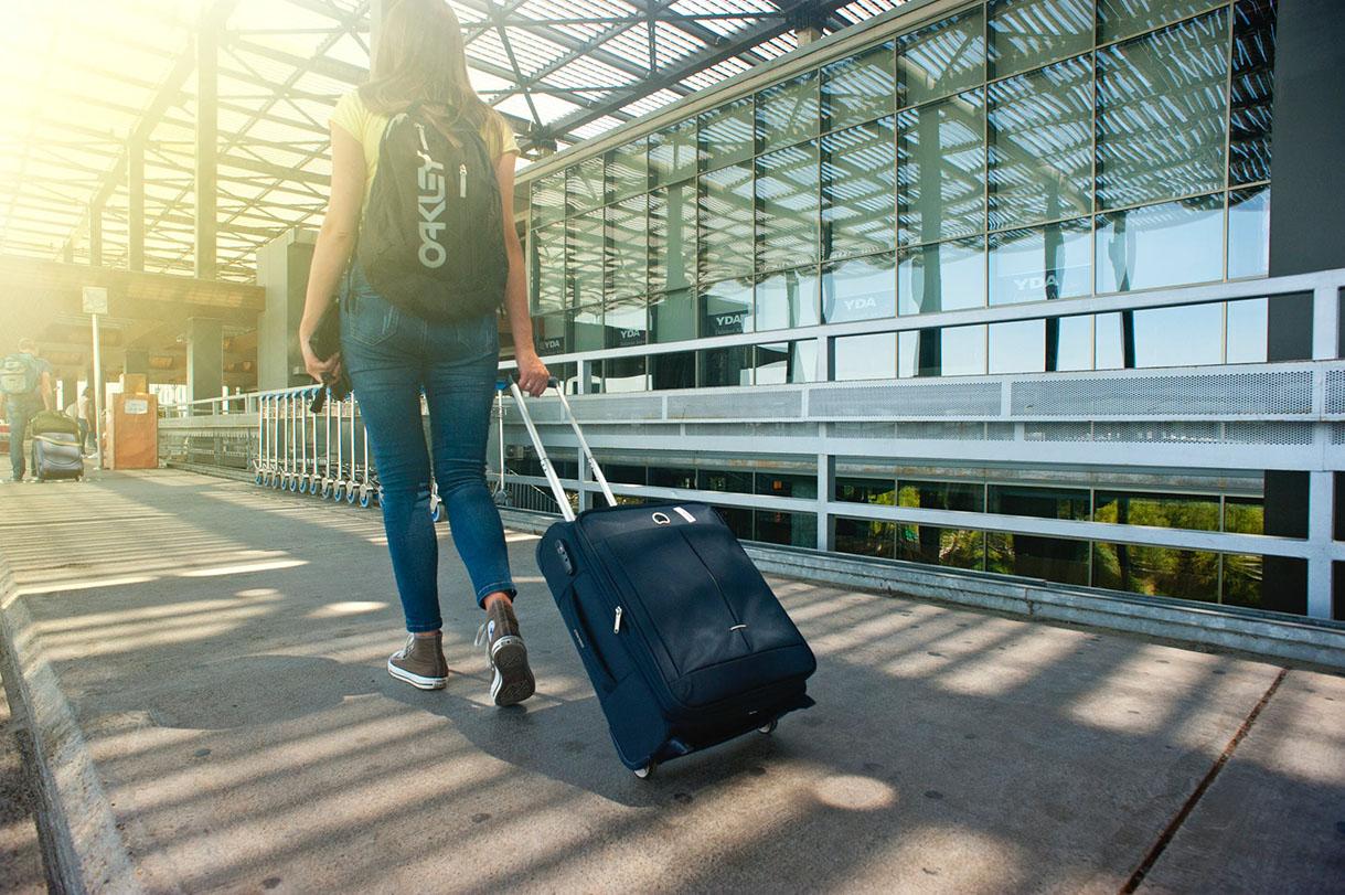 Joven con maleta en aeropuerto