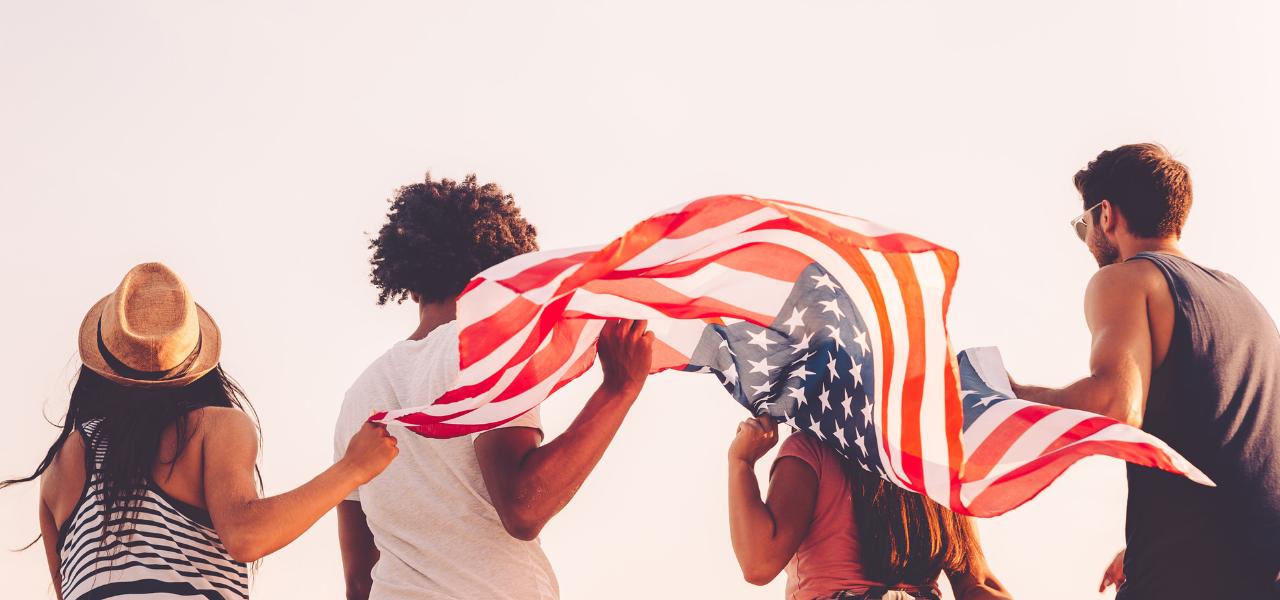 4 jóvenes sosteniendo bandera americana