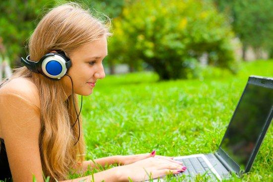 chica tumbada sobre el césped escuchando música con su ordenador